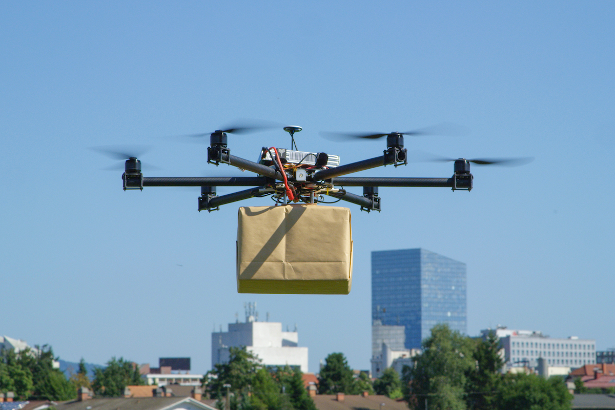 drone spinning in air holding a box wrapped up in brown paper