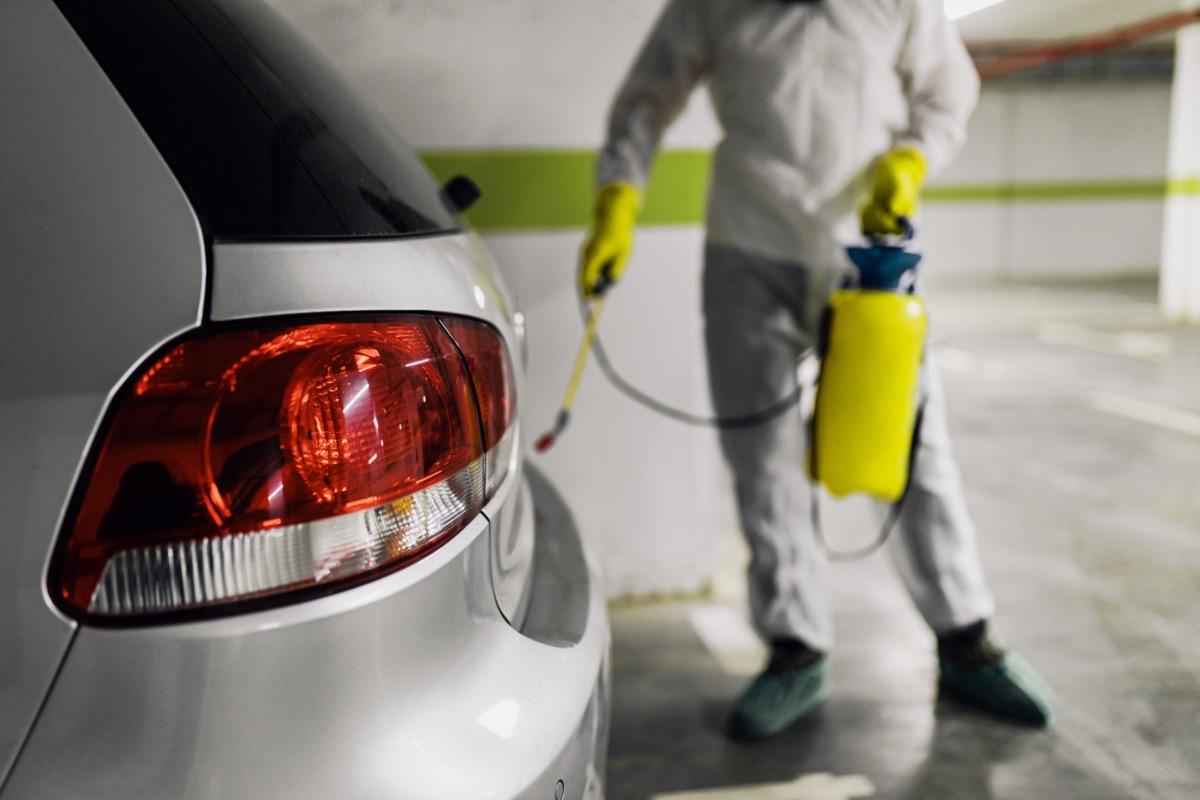 exterminator spraying car in garage