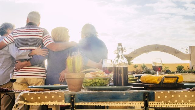 A group of four senior citizens gather for an outdoor celebration on Labor Day, with food and wine on a table as they look out over the city view.