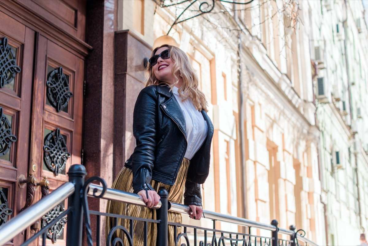 fashionable middle aged white woman with blonde hair leaning over railing