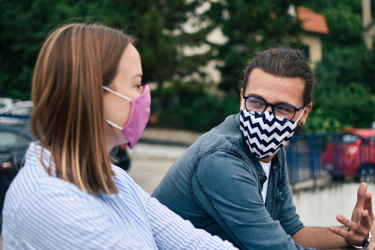 Young man and young woman wearing masks outside and talking