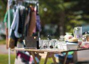 Garage sale clothing on rack and knick knacks on table.