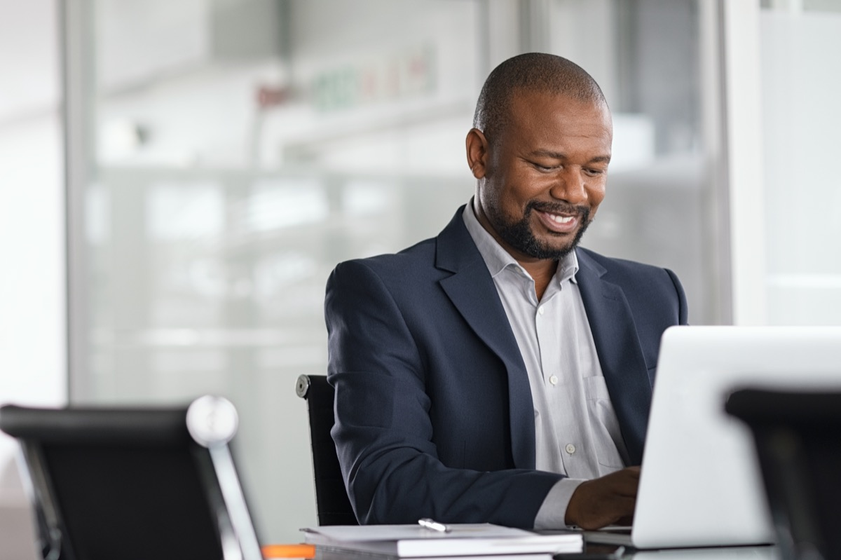 Positive mature businessman working on laptop in modern office. Successful african business man working on computer while sitting at desk. Smiling middle aged man working in a corporate.
