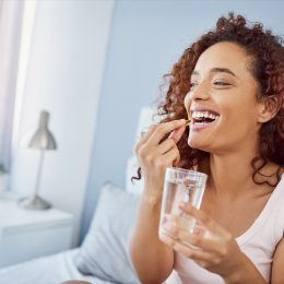 woman taking vitamins with water
