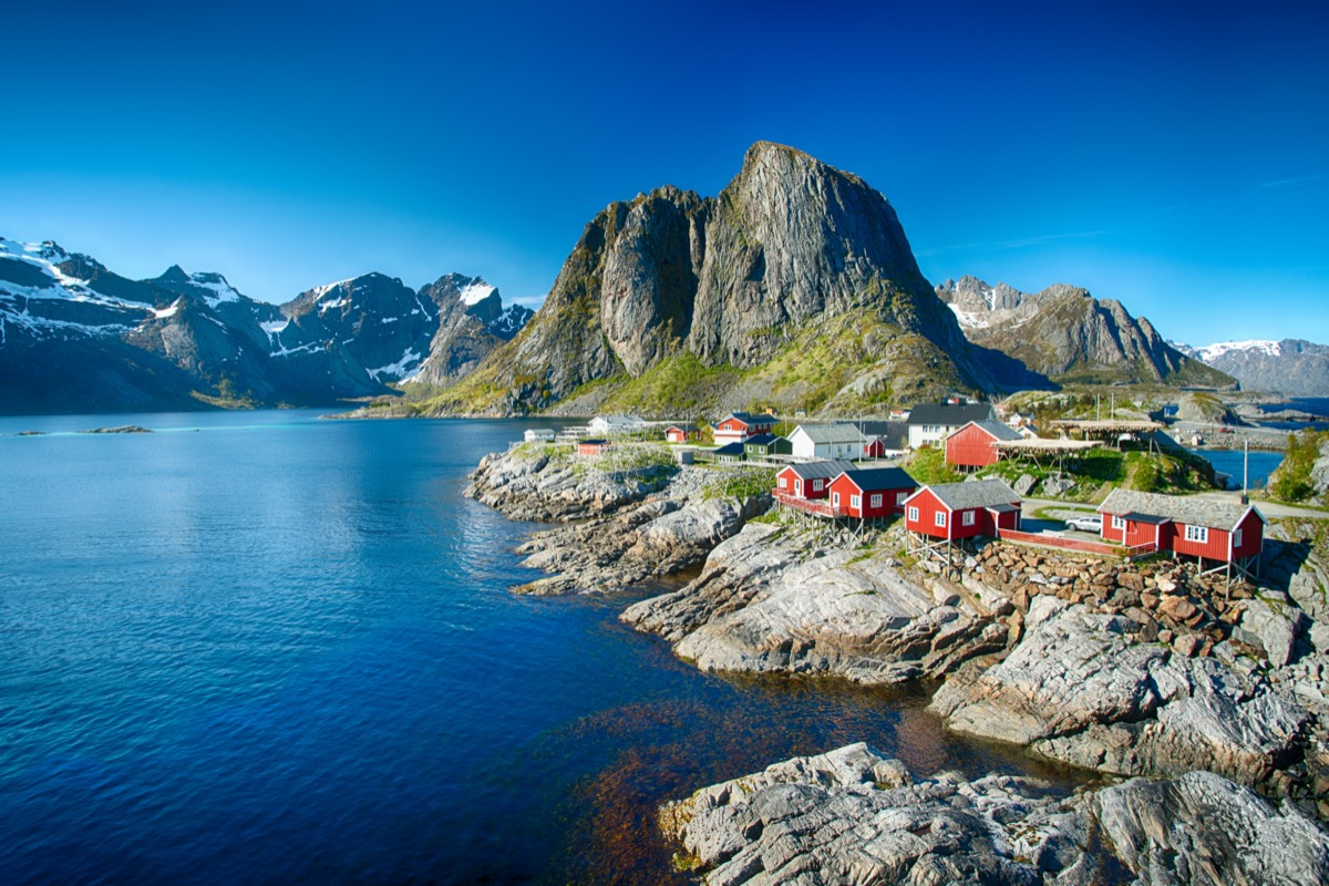 The village of Reine under a sunny, blue sky, with the typical red rorbu houses