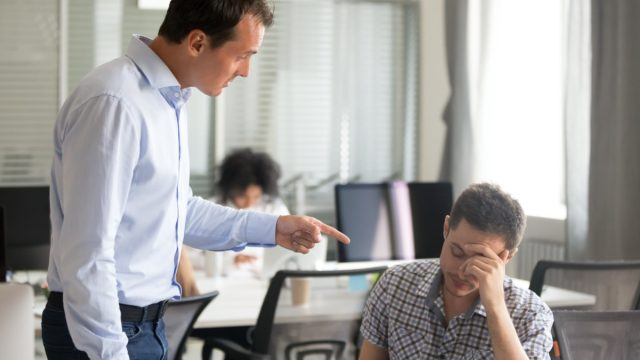 middle aged male boss yelling and pointing at employee