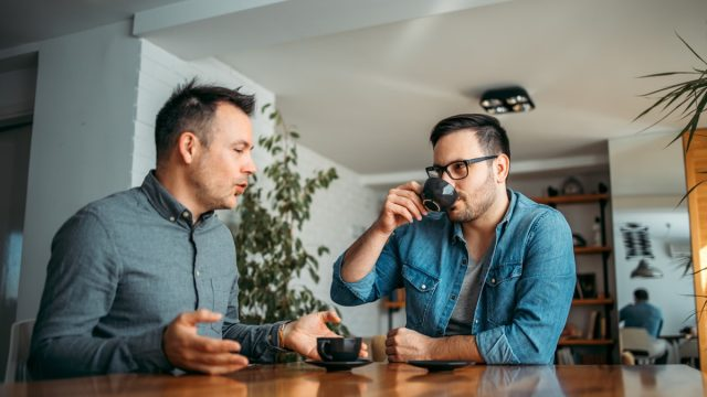 Two casual businessmen talking and drinking coffee at workplace