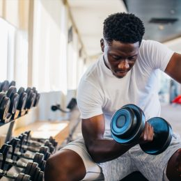 Young man sitting and lifting a dumbbell close to the rack at gym. Male weight training person doing a biceps curl in fitness center