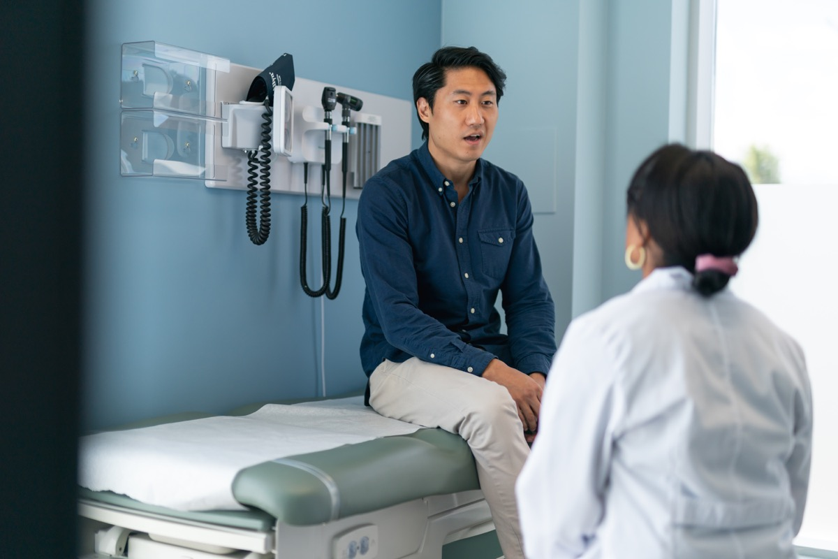 A man is at a routine medical appointment. The patient is sitting on an examination table facing his doctor. The kind doctor is listening as he speaks.