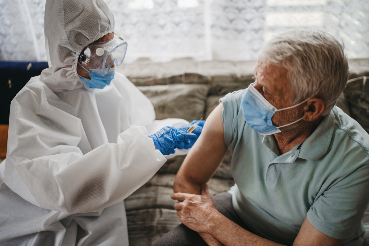 Female doctor in protective suit giving vaccine against covid19 virus to senior man at home