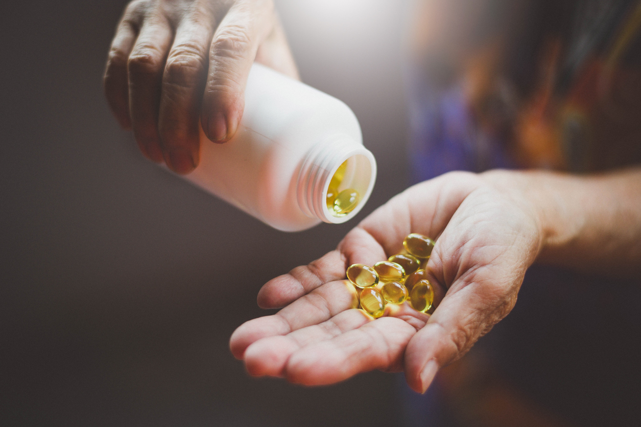 A man pouring out vitamin capsules from a white bottle into his hand.
