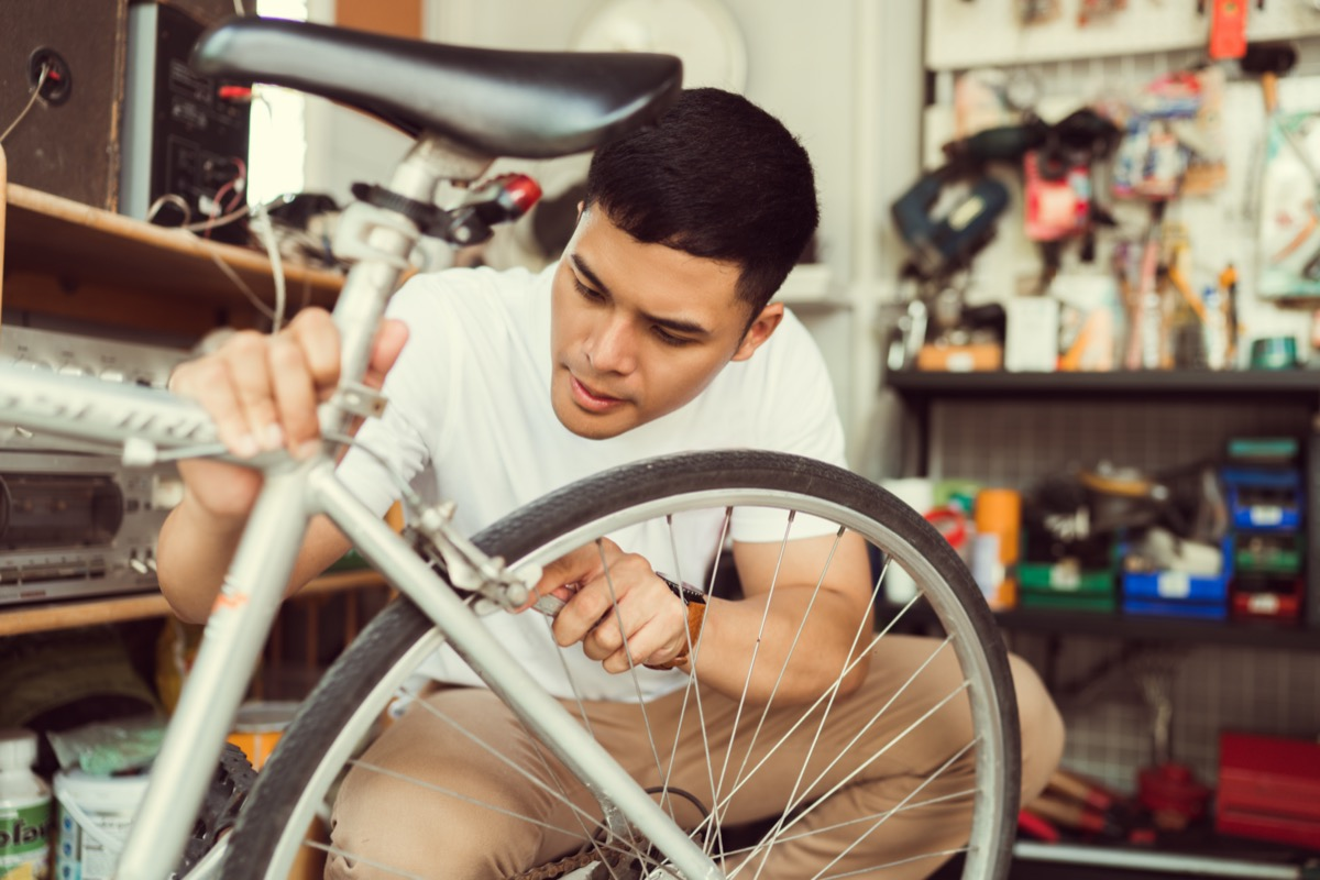 young man repairing bike tire