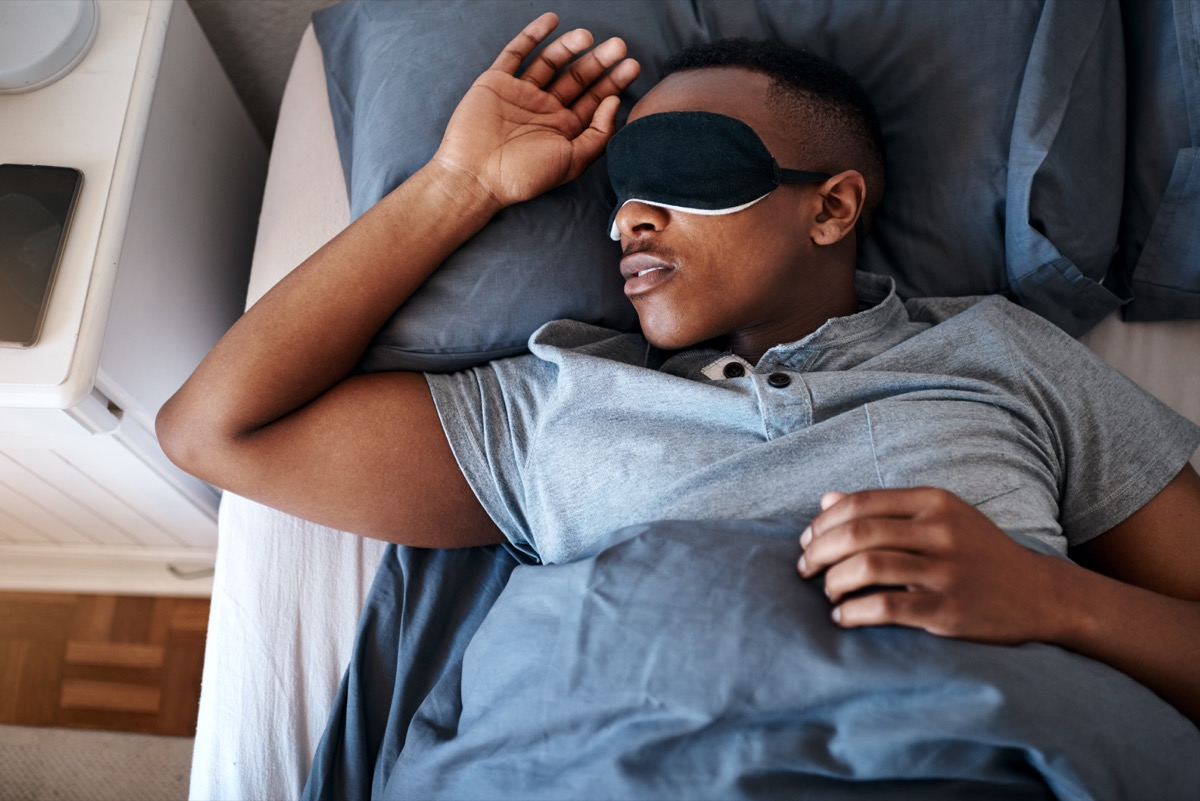Cropped shot of a handsome young man wearing a night mask and sleeping in his bed at home