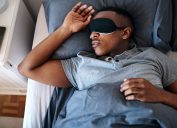 Young man wearing a night mask and sleeping in his bed at home