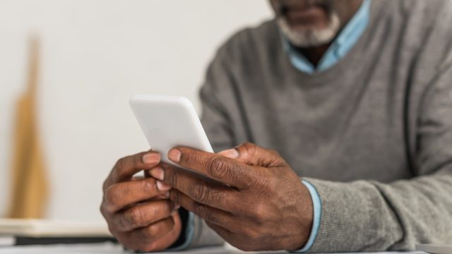 cropped view of senior man using smartphone while sitting at table