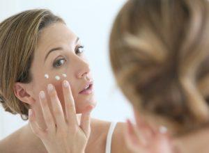 middle aged white woman applying eye cream