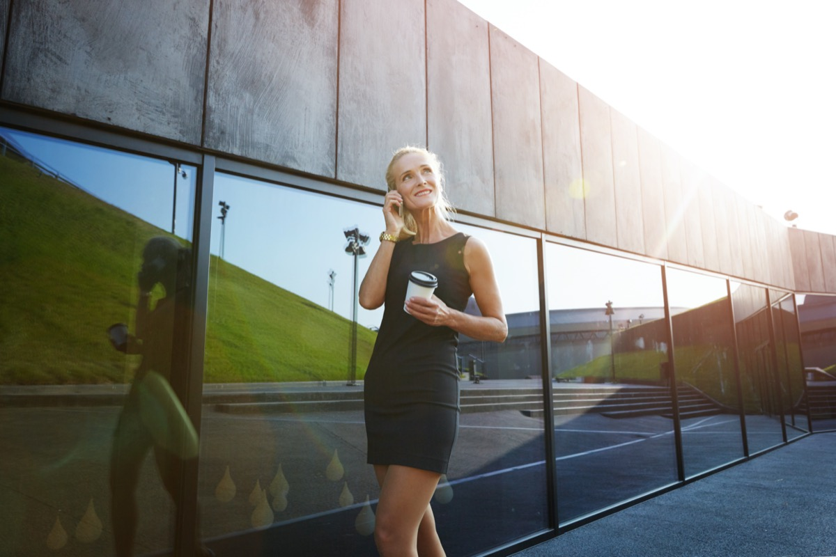 middle aged blonde woman wearing short dress outdoors