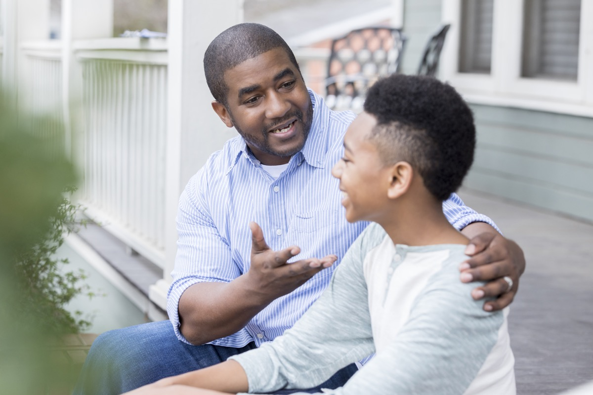 An excited mid adult father sits on the front steps of his home with his preteen son and gestures as they enjoy an exciting conversation.