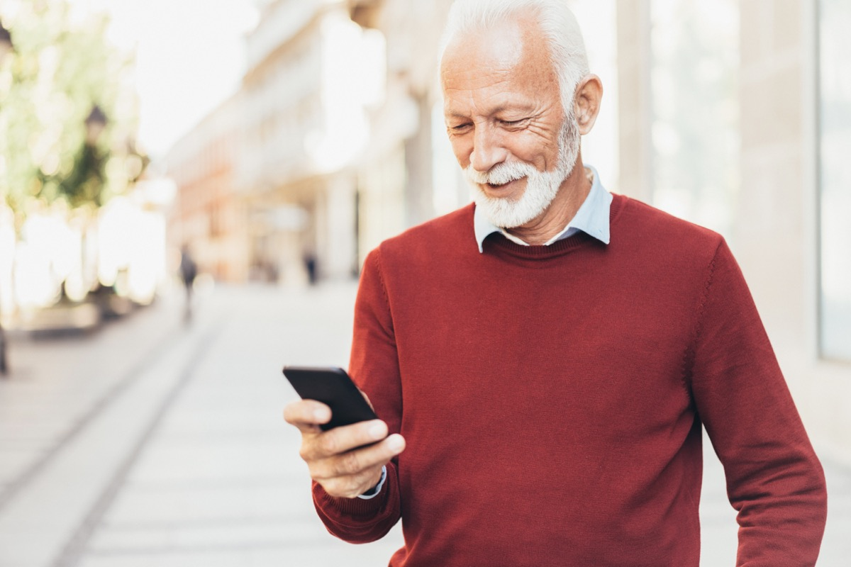 Smart casual senior man texting outdoor on the city street