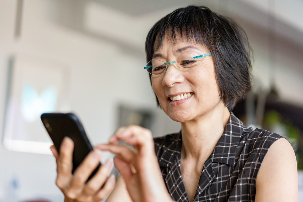 Senior Asian woman laughing when using a smartphone.
