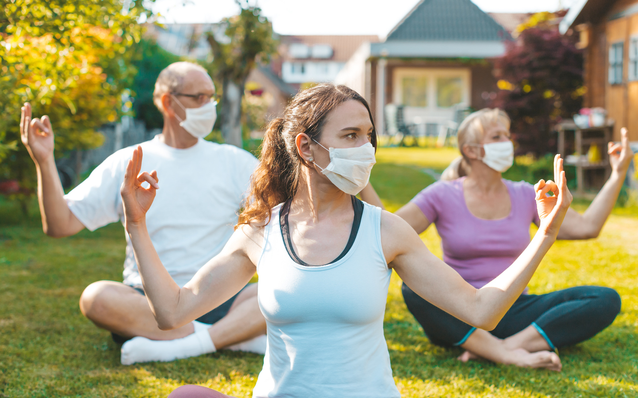 A group of mixed aged people do yoga outdoors with face masks on to stop the spread of COVID