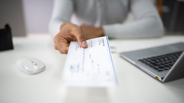 closeup of woman's hand handing over a paycheck