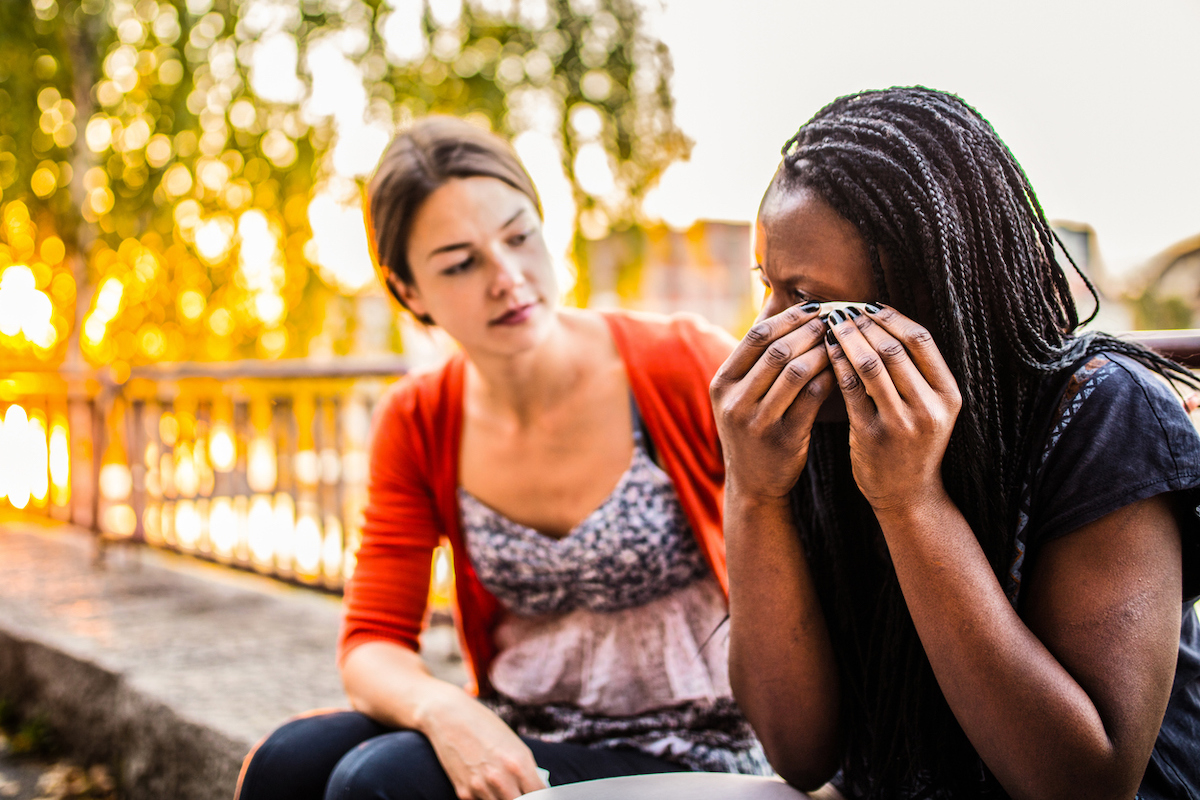 black woman crying while white woman comforts her