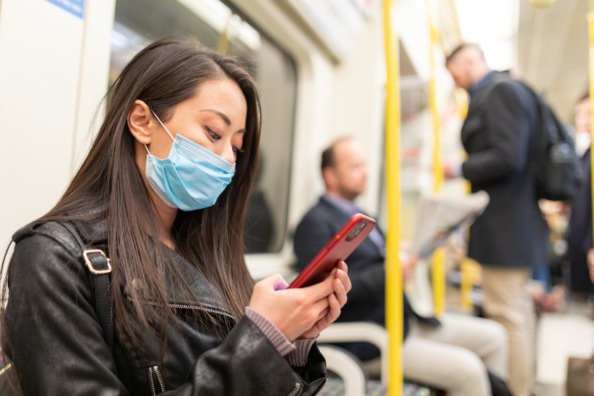Young woman wearing a face mask while travelling by tube to protect from coronavirus
