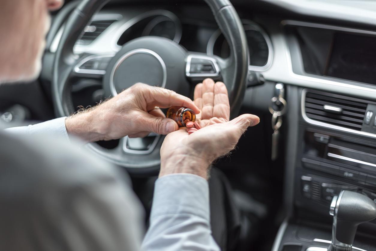 Man taking medicine before driving his car