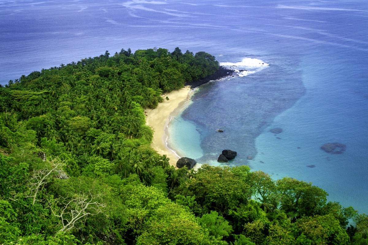 The most famous beach in Principe Island, the tiny island of São Tomé and Principe, on the west coast of Africa. This is perfect for swimming, with white sand curving in a banana shape around turquoise waters