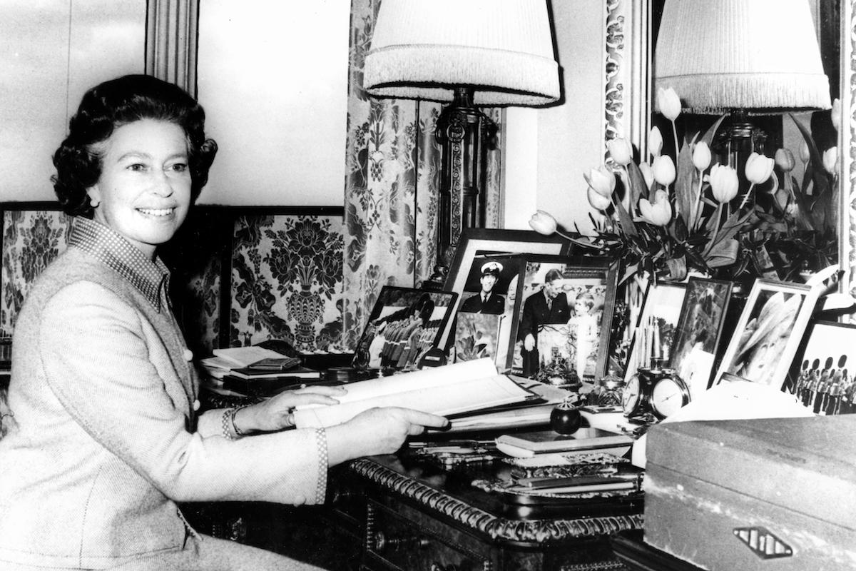 Queen Elizabeth II preparing for her silver jubilee tours, 1977, sitting at desk in front of photos and diary