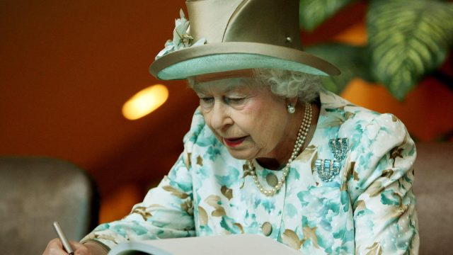 Queen Elizabeth II, 84, of Britain, signs a guest book after she addressed the General Assembly at the United Nations on July 6, 2010 in New York.