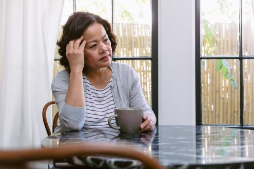 Upset senior woman drags her hand through her hair while staring out the window in her home. She is sitting at the kitchen table. A coffee cup is in front of her.