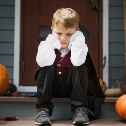 sad kid sitting on stoop, dressed up for halloween with cape, surrounded by pumpkins
