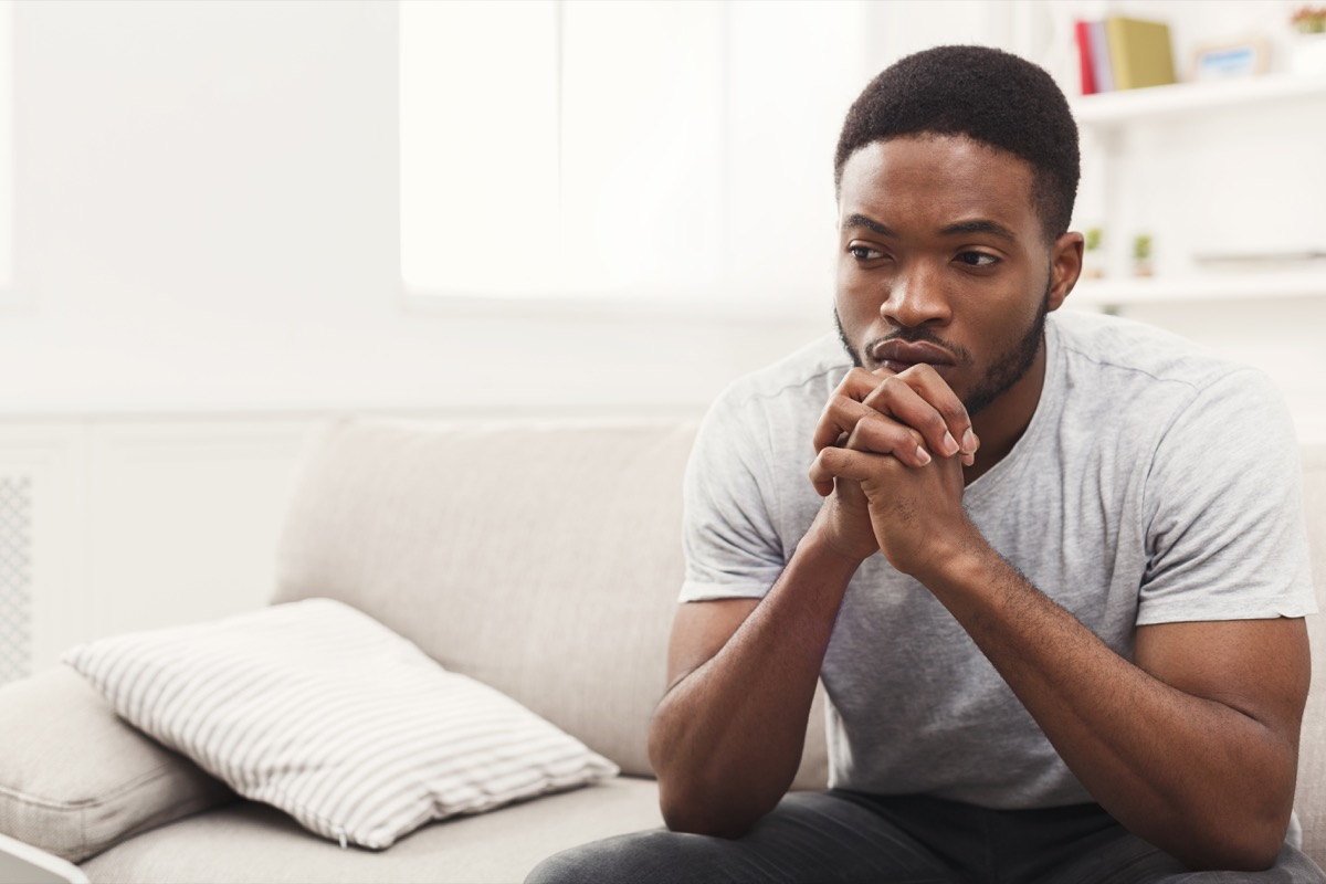 Young man sitting at home.  Sad guy sitting on the sofa, copy space