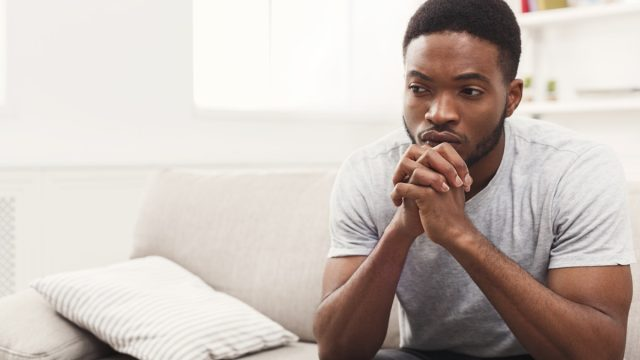 Young man sitting at home. Sad guy sitting on the couch , copy space