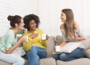three young women talking and drinking tea on the couch