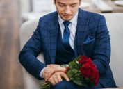 man in suit holding flowers and looking at watch