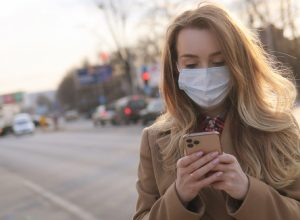 white woman with a face mask looking at her phone outside