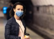 woman with a face mask and a coffee waiting for the train