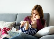 white mother holding sick son on couch