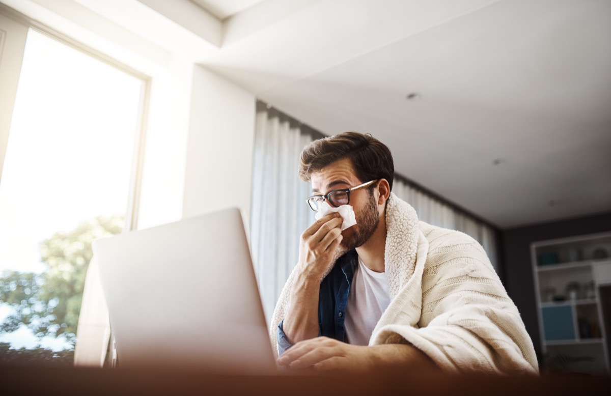 Shot of a sickly young businessman blowing his nose with a tissue while working from home