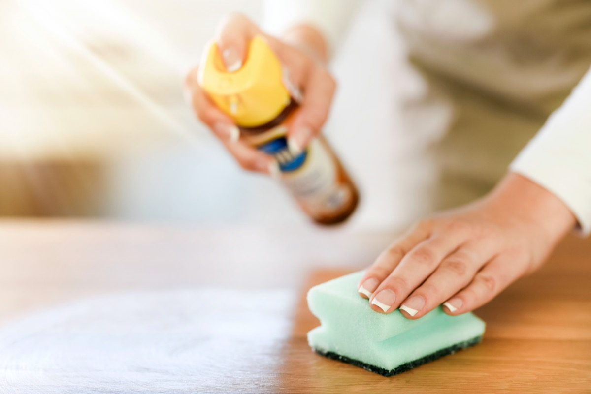 white hand cleaning wood with sponge