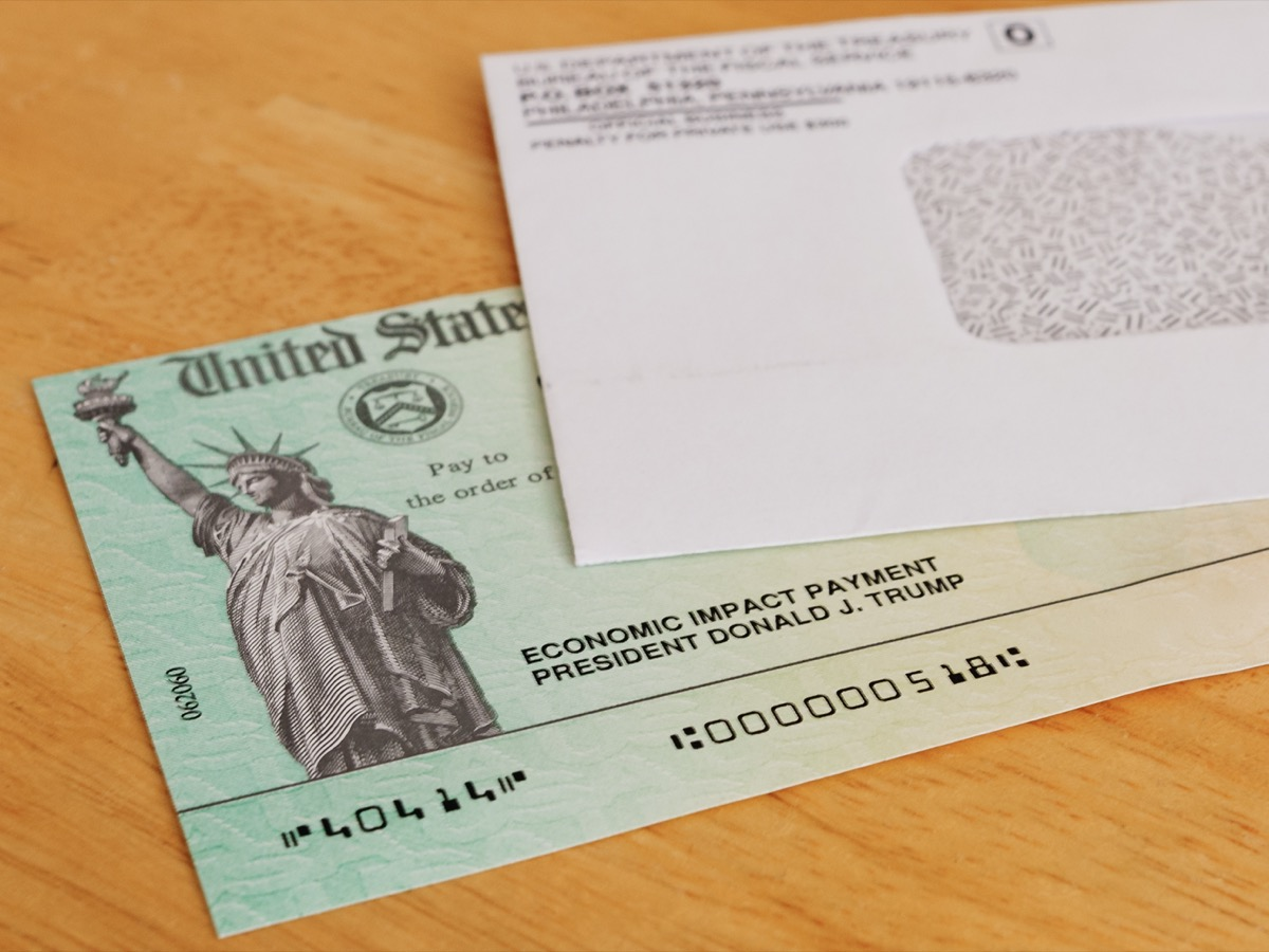stimulus check and envelope on a wooden table