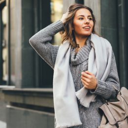 A stylish young woman standing on the street wearing a scarf and grey sweater.