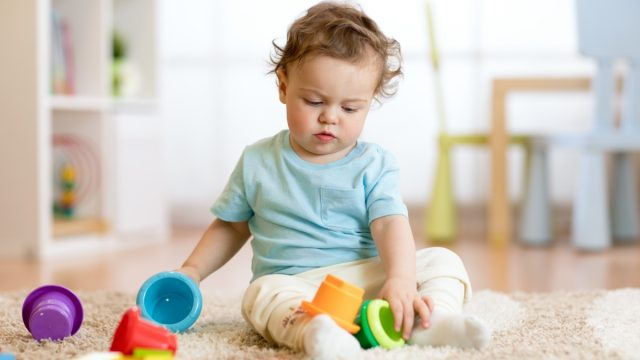 white toddler playing with stacking cups
