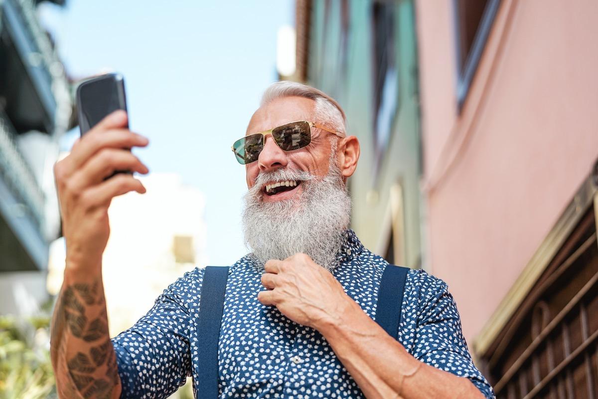 man with gray beard taking selfie