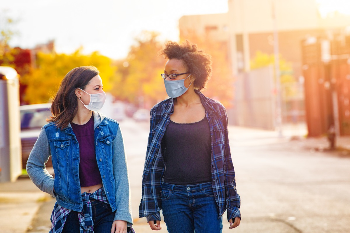 Two female friends walking down a Brooklyn alley wearing face masks on a sunny Autumn day, having a quiet conversation.