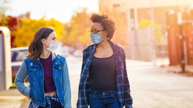 Two young female friends walk in an alleyway while talking to each other and wearing face masks.