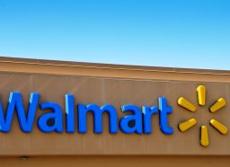 A blue Walmart sign and corporate logo on the front of a brown store.